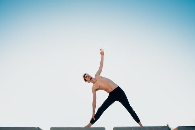 Jeune homme effectuant un exercice de mouvement commun inspiré par le yoga, à l'extérieur.