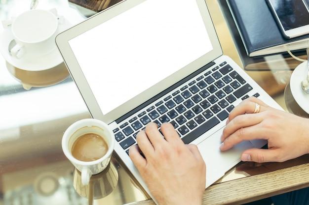 Jeune homme effectue un travail sur un ordinateur portable