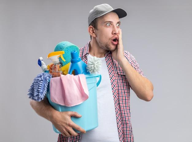 Un jeune homme effrayé portant une casquette tenant un seau avec des outils de nettoyage mettant la main sur la joue isolée sur un mur blanc