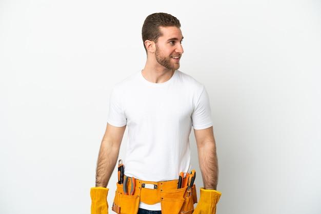 Jeune homme électricien isolé mur blanc regardant sur le côté et souriant