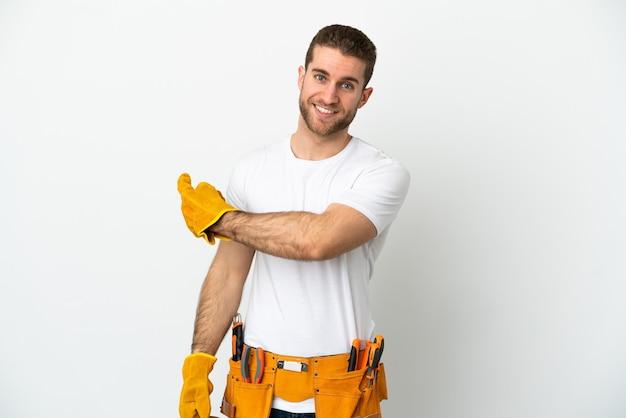 Jeune homme électricien sur mur blanc isolé pointant vers l'arrière