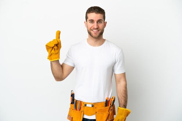 Jeune homme électricien sur un mur blanc isolé pointant vers une excellente idée
