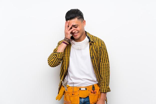 Jeune homme électricien sur mur blanc isolé souriant beaucoup