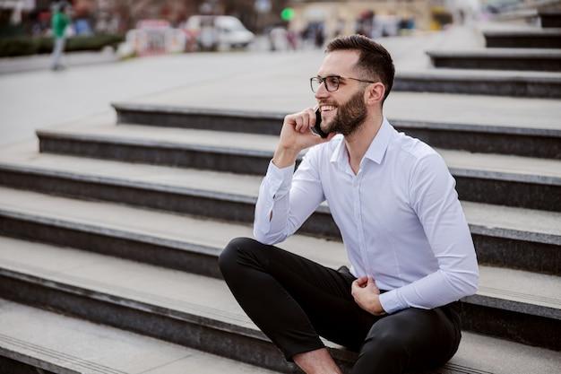 Jeune homme élégamment habillé assis sur les escaliers et ayant une conversation téléphonique.