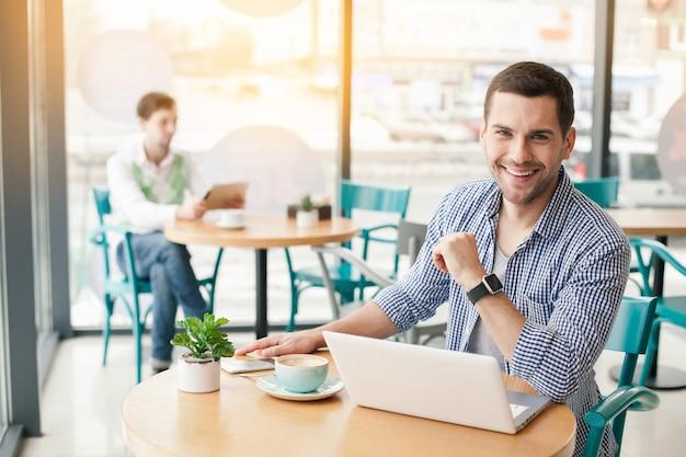 Jeune homme élégant au café
