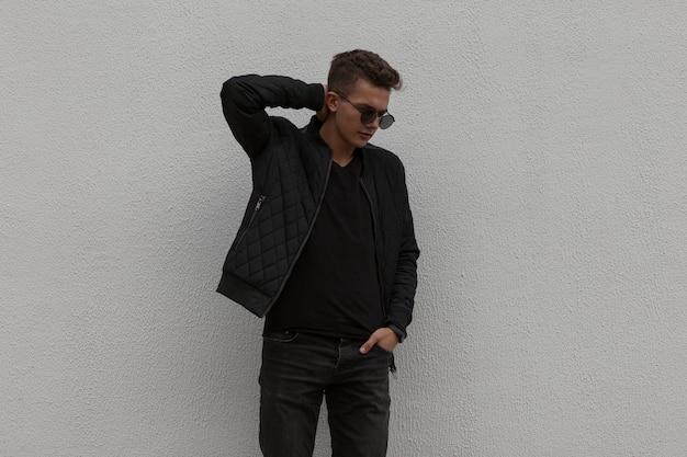 Jeune homme élégant beau modèle avec des lunettes de soleil dans des vêtements à la mode noirs près du mur gris