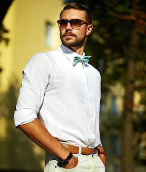 Jeune homme élégant beau modèle sexy dans un style de vie en tissu décontracté dans la rue dans des verres