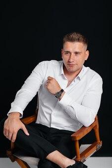 Un jeune homme élégant en chemise blanche est assis sur la chaise du réalisateur sur fond noir. un bel homme d'affaires charismatique.