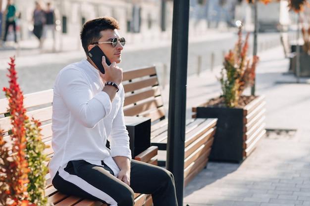 Jeune homme élégant en chemise avec téléphone sur banc par une chaude journée ensoleillée à l'extérieur
