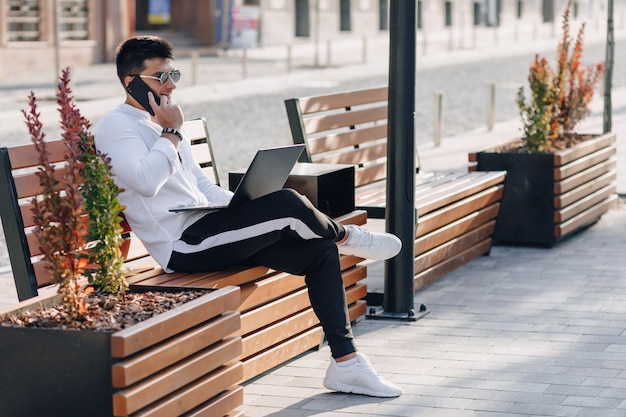 Jeune homme élégant en chemise avec téléphone et ordinateur portable sur un banc par une chaude journée ensoleillée à l'extérieur, freelance