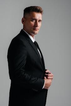 Un jeune homme élégant en costume d'affaires pose de côté sur un fond gris. un bel homme d'affaires charismatique.