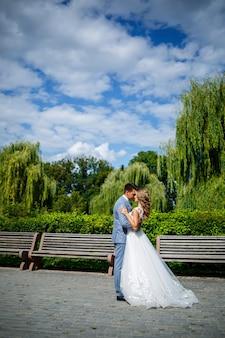 Jeune homme élégant en costume le marié et la mariée belle fille en robe blanche avec une promenade en train dans le parc le jour de leur mariage