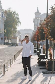 Jeune homme élégant dans une chemise marchant dans une rue européenne par une journée ensoleillée