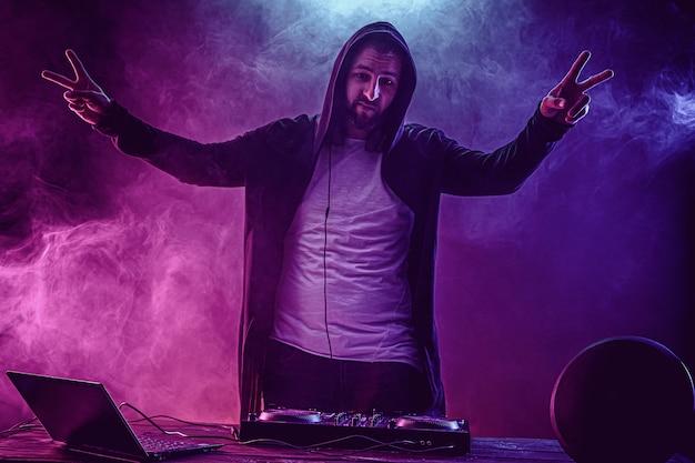 Jeune homme élégant dans des verres posant derrière la console de mixage sur studio de fumée colorée
