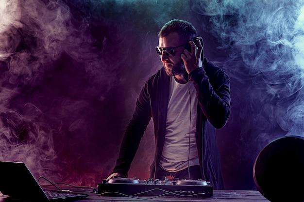 Jeune homme élégant dans des verres posant derrière la console de mixage