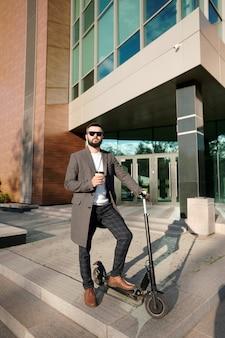 Jeune homme élégant dans des vêtements décontractés intelligents ayant un café à l'extérieur en se tenant debout sur un scooter électrique par l'architecture moderne