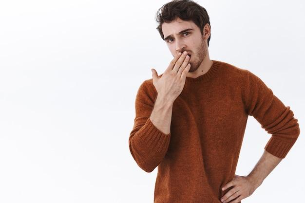 Un jeune homme élégant et désintéressé bâille alors qu'il entend une conversation ennuyeuse, le bâillement et la bouche ouverte semblent réticents