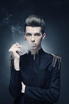 Jeune homme élégant fumant une cigarette