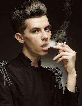 Jeune homme élégant, fumant une cigarette