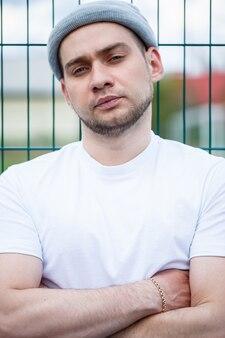 Jeune homme élégant, un homme vêtu d'un t-shirt blanc vierge et d'un chapeau gris debout sur fond de grille d'un terrain de football. style urbain de vêtements, image à la mode moderne. la mode masculine
