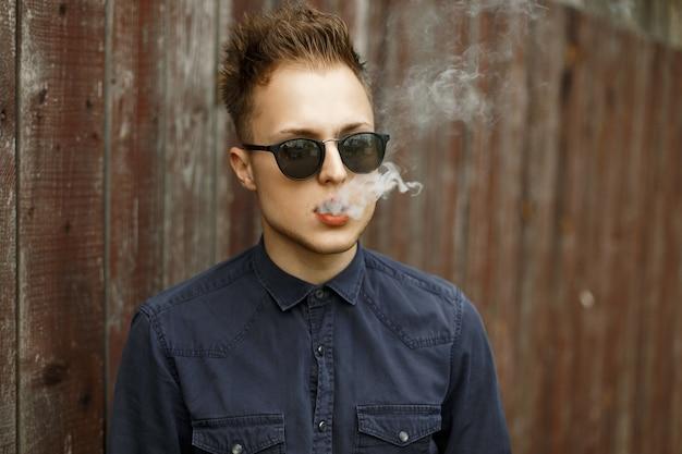 Jeune homme élégant à lunettes de soleil avec de la fumée fume une cigarette près d'un mur en bois