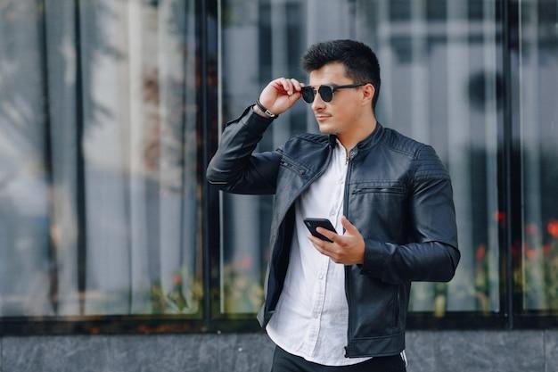 Jeune homme élégant à lunettes en veste de cuir noir avec téléphone sur la surface en verre