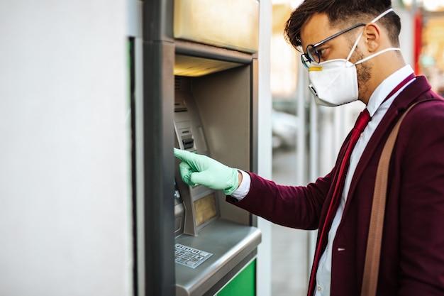 Jeune homme élégant avec masque de protection debout dans la rue de la ville et utilisant un distributeur automatique de billets avec des gants de protection sur les mains. concept de prévention des pandémies de virus et de soins de santé.