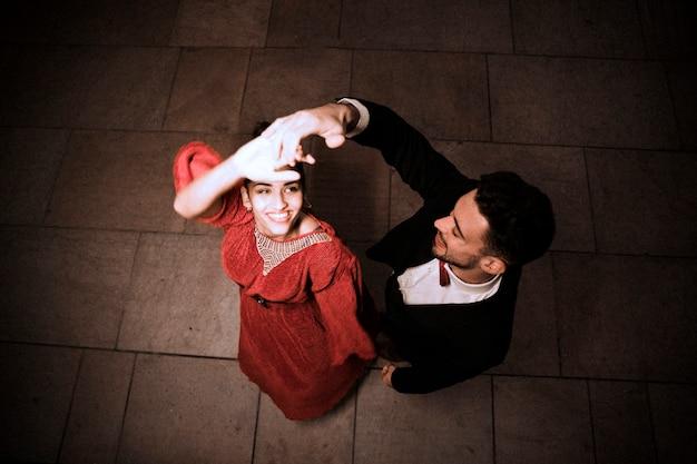 Jeune homme élégant, tenant la main de la danse charmante femme joyeuse