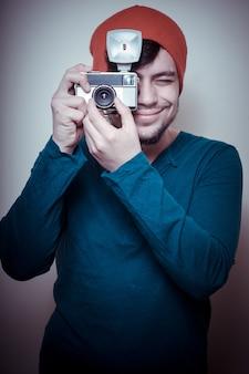 Jeune homme élégant tenant le vieil appareil photo