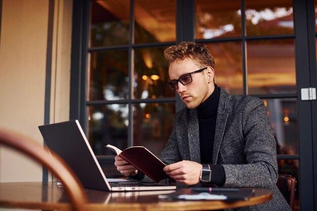 Un jeune homme élégant en tenue de soirée est assis dans un café avec son ordinateur portable et lit le livre.