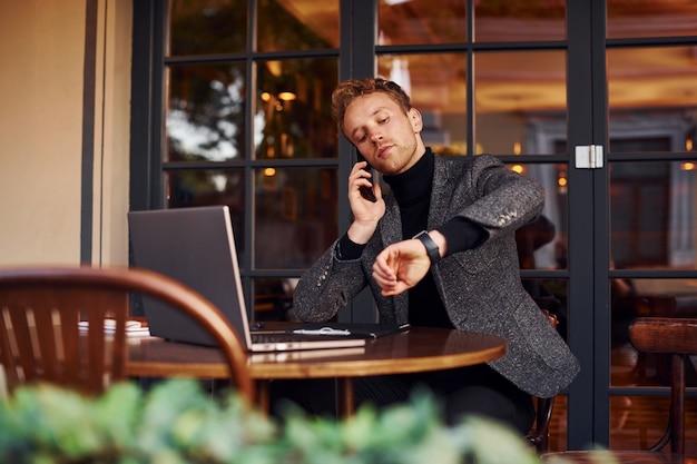 Un jeune homme élégant en tenue de soirée est assis dans un café avec son ordinateur portable et parle par téléphone.