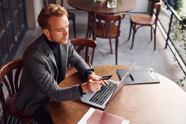 Un jeune homme élégant en tenue de soirée est assis dans un café avec son ordinateur portable et sa carte de crédit en main.