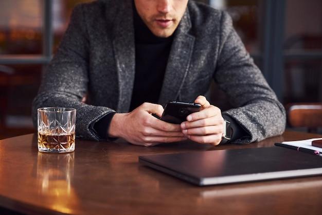 Un jeune homme élégant en tenue de soirée est assis dans un café avec son ordinateur portable et son téléphone dans les mains.