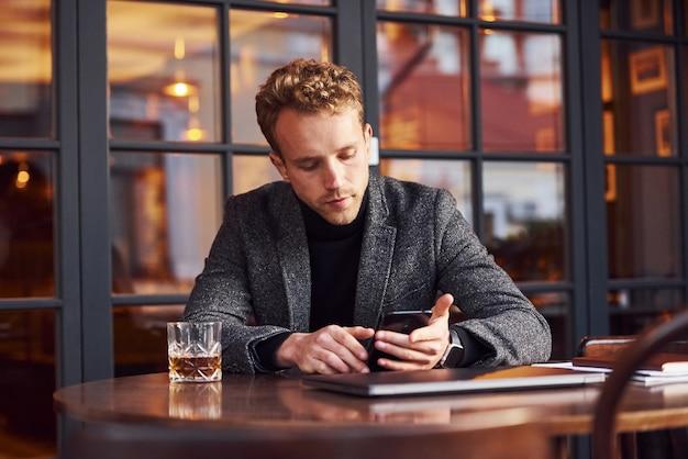 Un Jeune Homme élégant En Tenue De Soirée Est Assis Dans Un Café Avec Son Ordinateur Portable Et Son Téléphone Dans Les Mains. Photo Premium