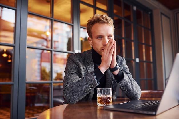 Un jeune homme élégant en tenue de soirée est assis dans un café avec son ordinateur portable et son verre d'alcool.