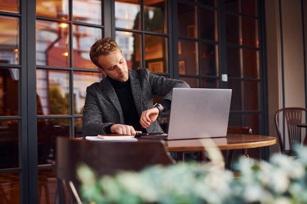 Un jeune homme élégant en tenue de soirée est assis dans un café avec son ordinateur portable et vérifie l'heure.
