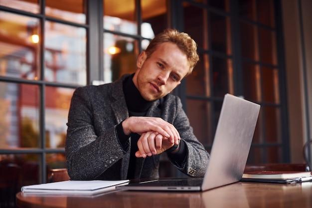 Un jeune homme élégant en tenue de soirée est assis dans un café avec son ordinateur portable.