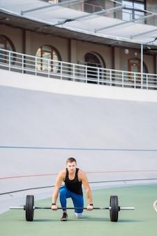 Un jeune homme élève la barre dans le stade, entraînement en plein air