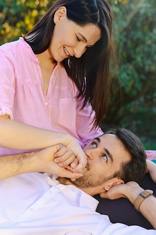 Jeune homme embrassant doucement la main de sa femme tout en la regardant happ