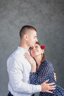 Jeune homme embrassant une femme en robe bleue