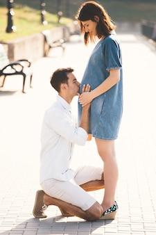 Jeune homme embrassant le ventre de sa femme enceinte en position debout