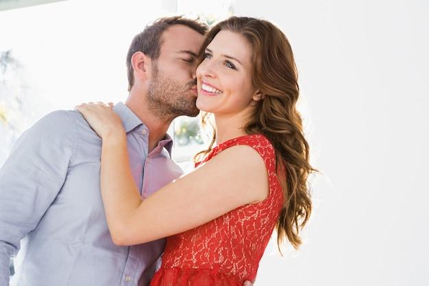 Jeune homme embrasse une belle femme sur la joue