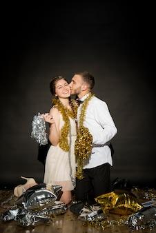 Jeune homme embrasse une dame souriante en tenue de soirée avec des guirlandes sur le sol