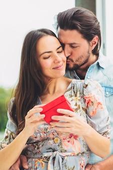 Jeune homme embrasse une femme avec un cadeau sur la joue
