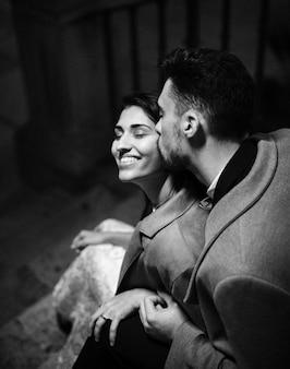 Jeune homme embrasse une femme heureuse dans les escaliers
