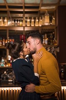 Jeune homme, embrasser, et, étreindre, à, femme, près, bar, comptoir