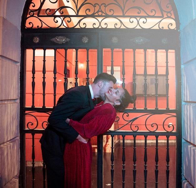 Jeune homme, embrasser, plier, attrayant, femme gaie, sur, rue