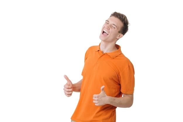 Jeune homme émotif aux cheveux bruns criant et montrant les pouces vers le haut, se sentant excité. notion de réussite