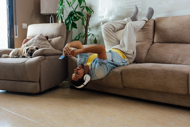 Jeune homme émotionnel bavardant en ligne au téléphone à la maison