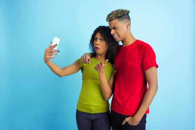 Jeune homme émotionnel et femme dans des vêtements colorés sur bleu.